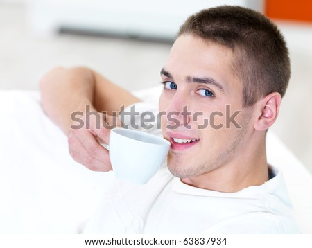 smiling young man with cup of coffee  at home - stock photo
