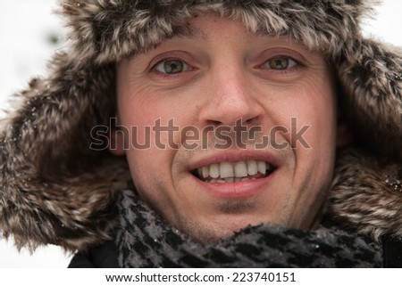Smiling young man with fur winter hat with ear flaps - stock photo