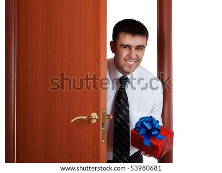 smiling young man with gift opening the door - stock photo