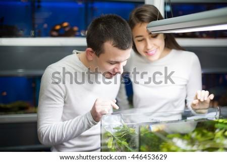 Smiling young man with girlfriend choosing aquarium fish in aquarium - stock photo