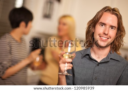 Smiling Young Man with Glass of Wine Socializing in a Party Setting.