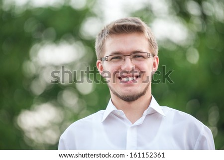 Smiling young man with glasses on bokeh background - stock photo