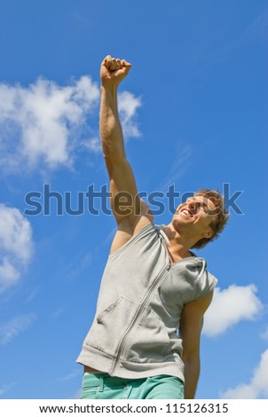 Smiling young man with his arm raised in joy, outdoors on a sunny day. - stock photo