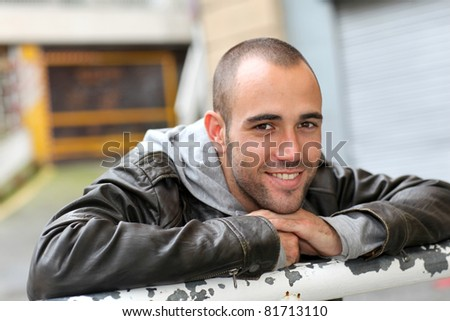 Smiling young man with leather jacket in town - stock photo