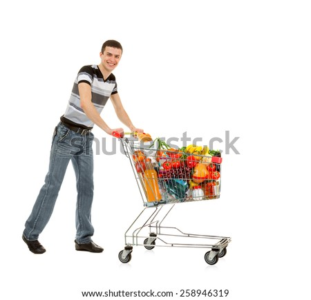 Smiling Young Man with Shopping Cart full of Food and Drink on the White Background