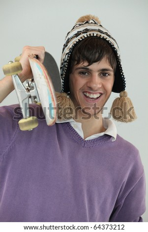 Smiling young man with skateboard - stock photo