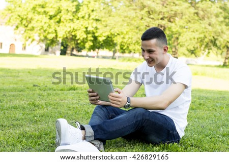 Smiling young man with tablet in park - stock photo