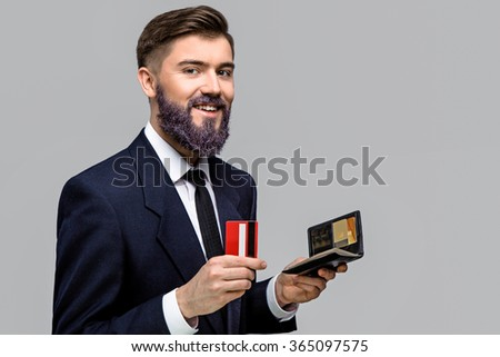 Smiling young man, with violet beard, wearing in dark blue suit and tie, holding wallet and credit card in his hands, on gray background, in studio, waist up - stock photo