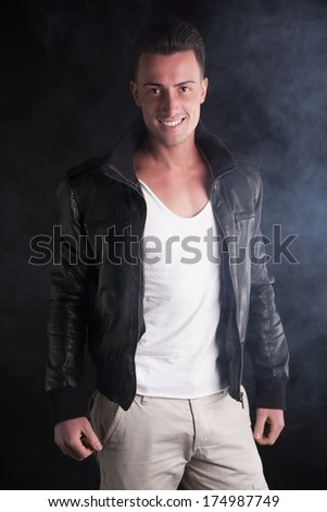 Smiling young man with white t-shirt and black leather jacket. Smoke and dark background