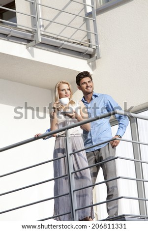 Smiling young man with woman having coffee at hotel balcony - stock photo
