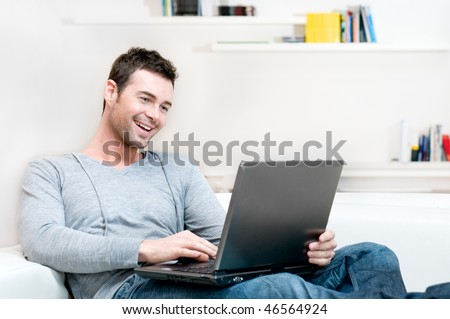 Smiling young man working on laptop at home copy space - stock photo