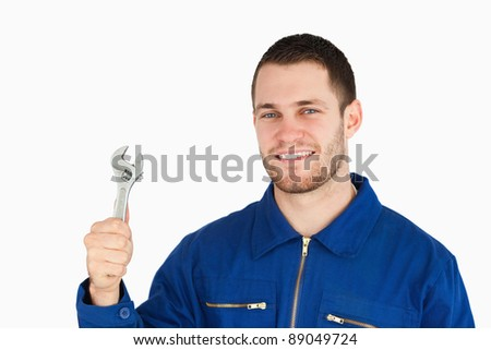 Smiling young mechanic holding his wrench against a white background - stock photo