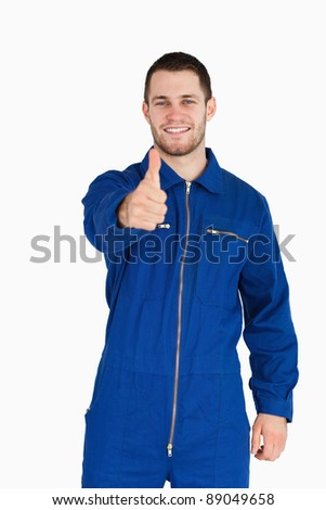 Smiling young mechanic in boiler suit giving thumb up against a white background - stock photo