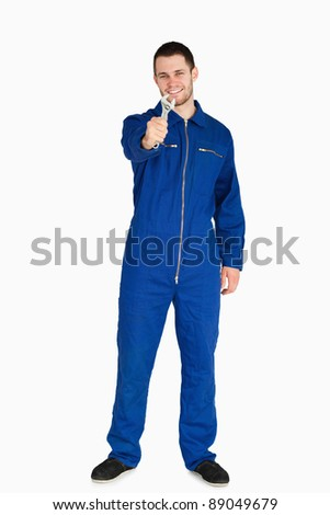 Smiling young mechanic in boiler suit presenting his wrench against a white background - stock photo