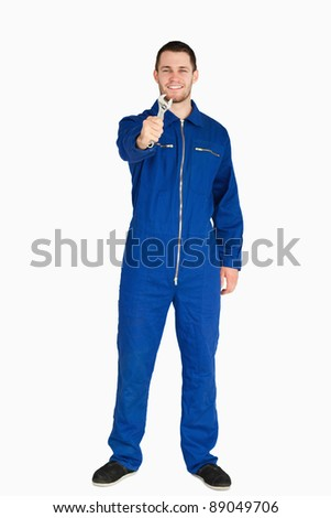 Smiling young mechanic in boiler suit showing his wrench against a white background - stock photo