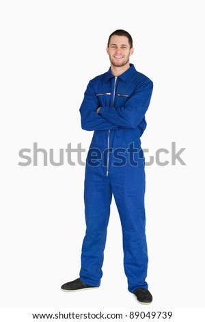Smiling young mechanic in boiler suit with arms folded against a white background