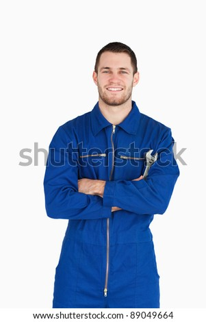 Smiling young mechanic in boiler suit with wrench and arms folded against a white background - stock photo