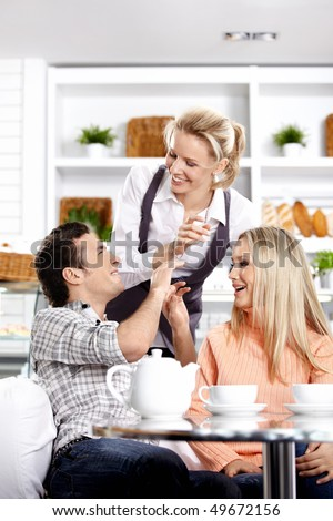 Smiling young men behind a table in cafe - stock photo
