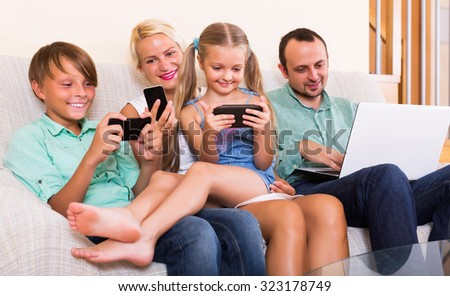 Smiling young mom, dad and two kids working with smartphones indoors