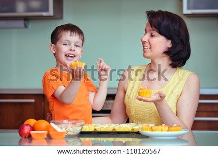 Smiling young mother and her little son baking muffins in the kitchen