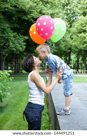 Smiling young mother and son spend time together in the park - stock photo