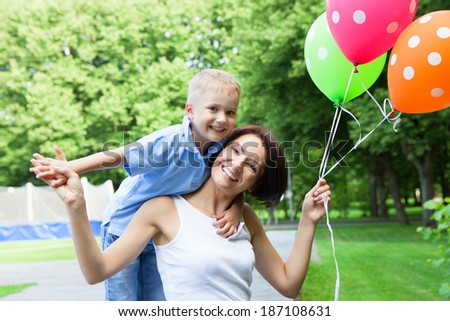 Smiling young mother and son spending time together in a summer park
