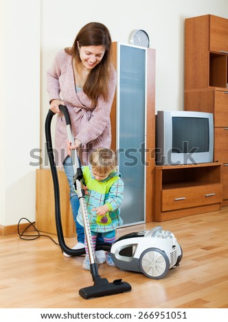 Smiling young mother with child cleaning living room with vacuum cleaner - stock photo
