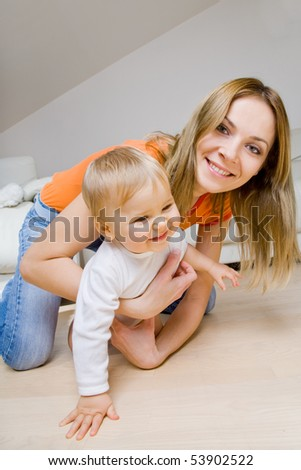 smiling young mother  with her baby having fun - stock photo