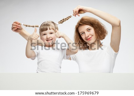 Smiling young mother with her funny  daughter, neutral background - stock photo