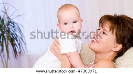 Smiling young mum and baby in a home interior