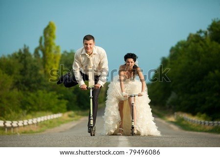 Smiling young newlywed couple with scooter on countryside road - stock photo