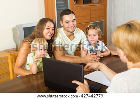 Smiling young parents and two daughters sitting in front of social worker - stock photo