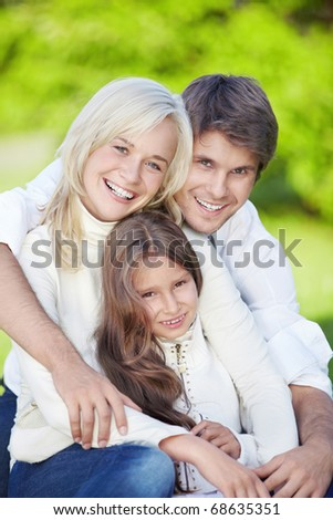 Smiling young parents with daughter outdoors - stock photo
