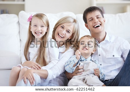 Smiling young parents with two children at home - stock photo