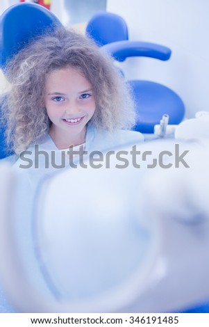 Smiling young patient sitting in dentists chair at the dental clinic - stock photo