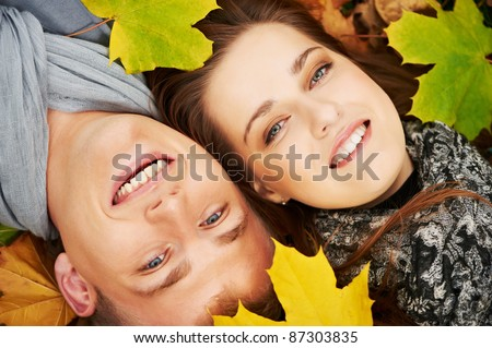 Smiling young people couple lying down on autumn maple leaves at fall outdoors - stock photo