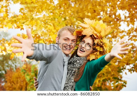 Smiling young people couple with open arms at fall outdoors. Woman wear autumn maple leaves wreath - stock photo