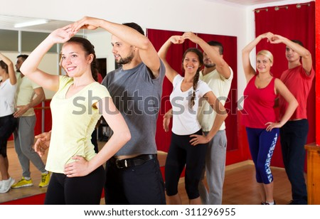 Smiling young people dancing Latino dance in class  - stock photo