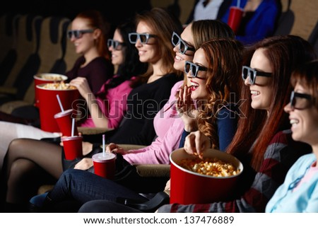 Smiling young people in the cinema - stock photo