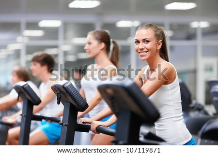 Smiling young people on treadmills - stock photo