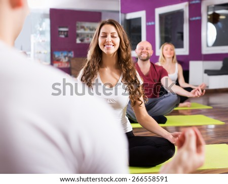 Smiling young people studying new position at yoga school - stock photo