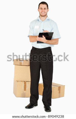 Smiling young post employee with parcels and clipboard against a white background - stock photo