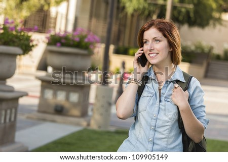Smiling Young Pretty Female Student with Backpack Walking Outside Using Cell Phone. - stock photo