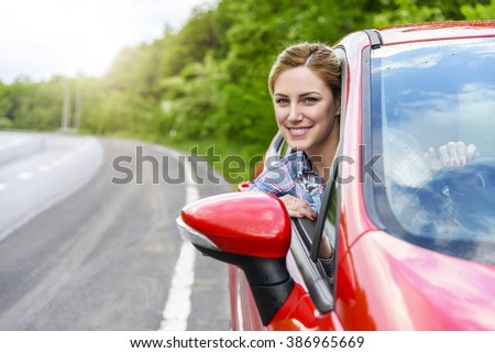 Smiling young pretty woman in the red car. Concept of travel, rent car or buying car.  - stock photo