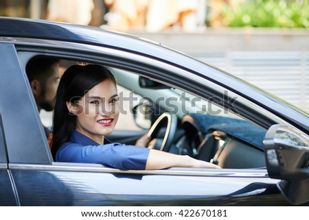 Smiling young pretty woman sitting in car