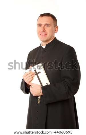 Smiling young priest with bible and rosary in his hands - stock photo