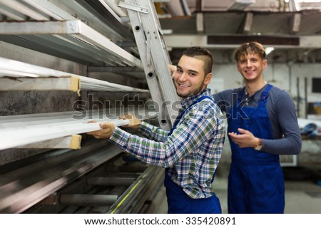Smiling young production workmen in uniform with different PVC window profiles - stock photo
