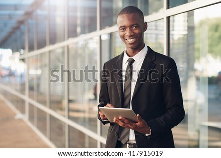 Smiling young professional African man with a digital tablet  - stock photo