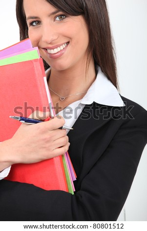 Smiling young professional woman with multi-colored folders - stock photo