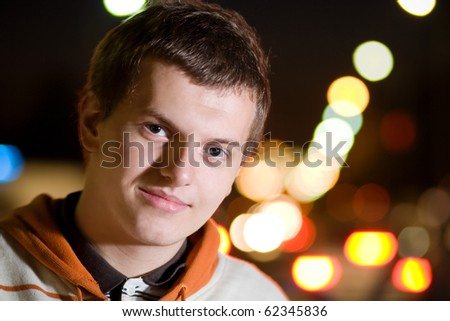 Smiling young rapper guy outdoors in the dark time of the day - stock photo